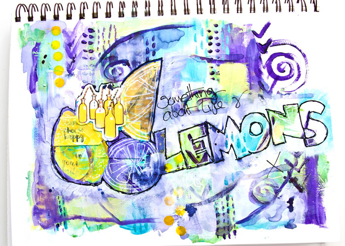 An art journal page with lemons written and drawn on it using acrylic paints